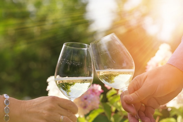 Couple romantically celebrate outdoors with glasses of white wine, proclaim toast people having dinner in a home garden in summer sunlight.