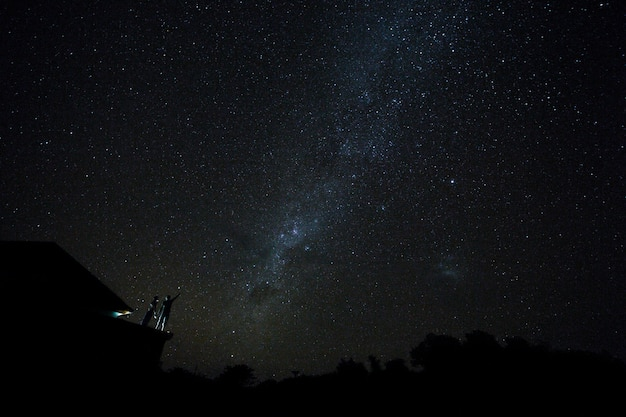 Couple on rooftop watching mliky way and stars in the night sky on bali island.
