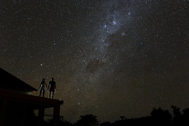 Couple on rooftop watching mliky way and stars in the night sky on bali island