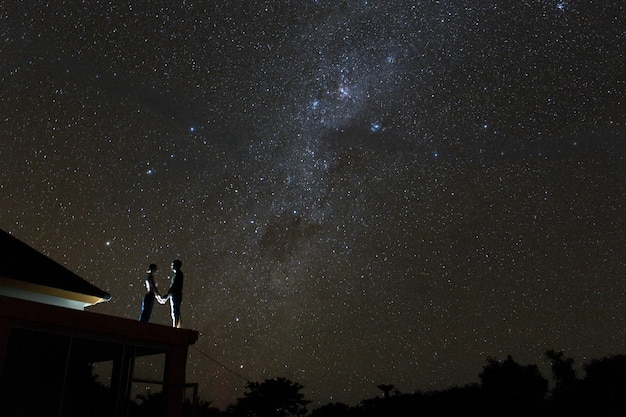Couple on rooftop watching mliky way and stars in the night sky