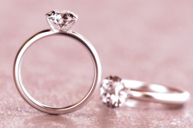 Couple of round diamond cut ring isolated on pink background, 3d rendering.