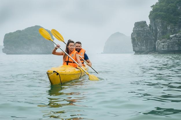Halong bay의 안개와 안개로 뒤덮인 바다에서 카약을 노 젓는 커플 하롱베이는 스포츠 카약과 탐험으로 인기 있는 관광지입니다.