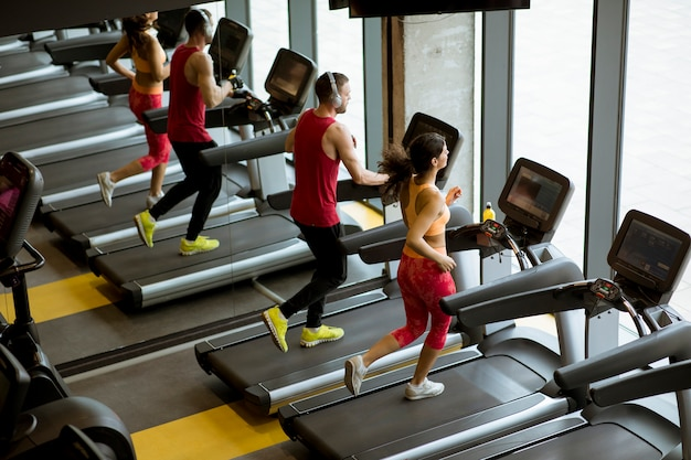 Couple run on treadmills in the gym
