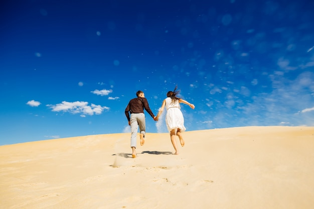 Couple running across the sand and holding hands
