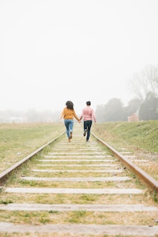 Couple running along railway and holding hands