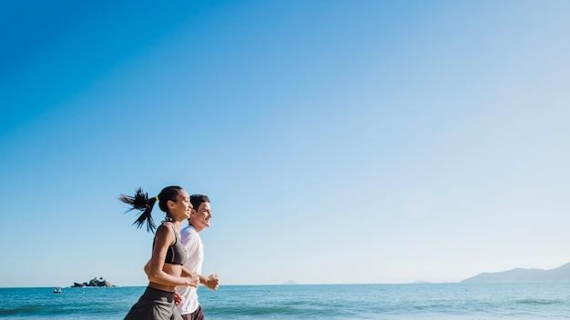 砂浜の下でビーチで走っているカップル