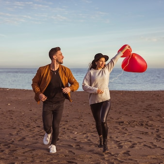 Couple running on sea shore with heart balloons