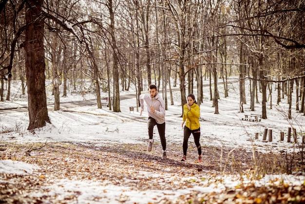 冬の森の中で並んで走っているカップル。