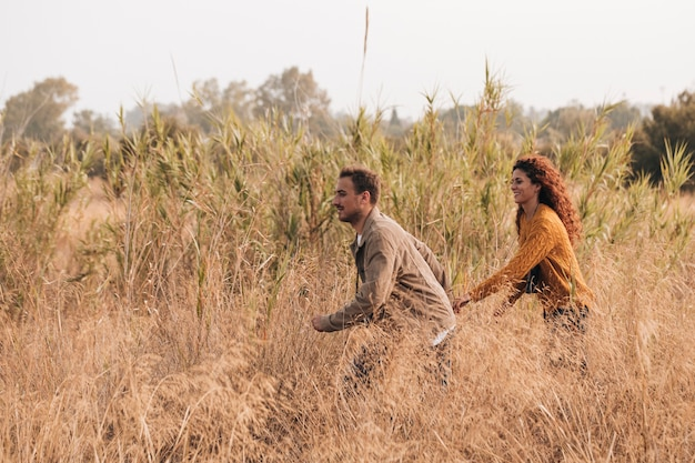 Couple running through wheat field