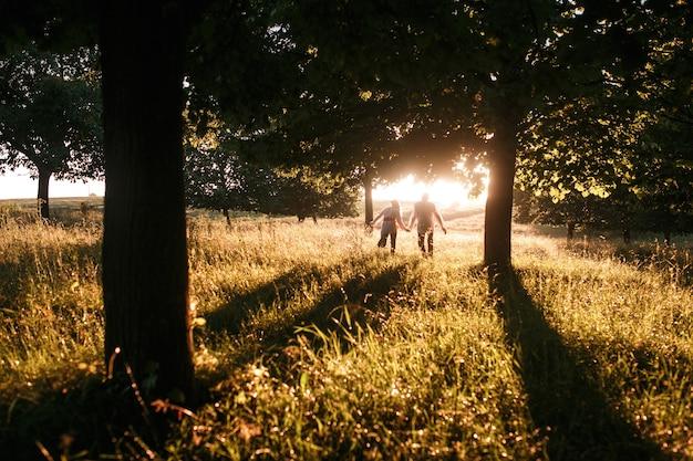 夕日に向かって走っているカップル