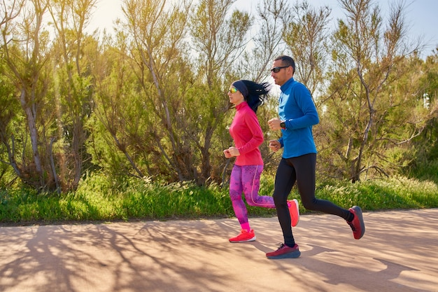 Пара работает. женщина и мужчина тренируются вместе на природе в приятный и теплый день. яркие цвета и солнечный свет