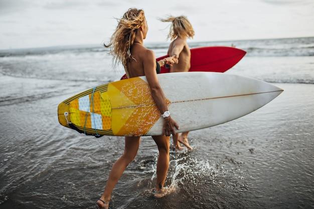 カップルは海岸に沿って海へと走ります。男性と女性がサーフィンをします