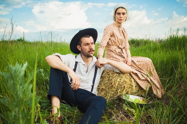Couple in rural clothing sitting in the field