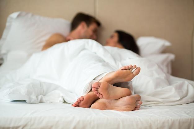 Ноги пары в постели.