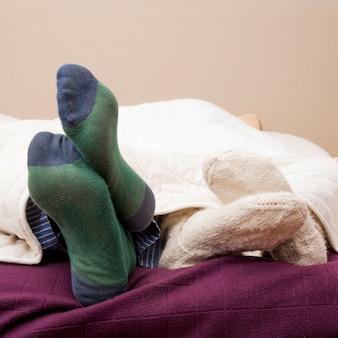 Couple's feet wearing socks under the bed sheet