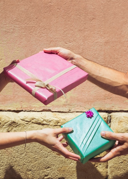 Couple's hand giving valentine gift to each other in front of wall