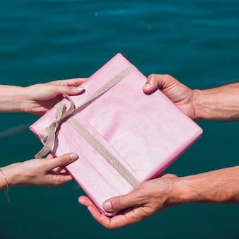 Couple's hand holding gift in front of sea
