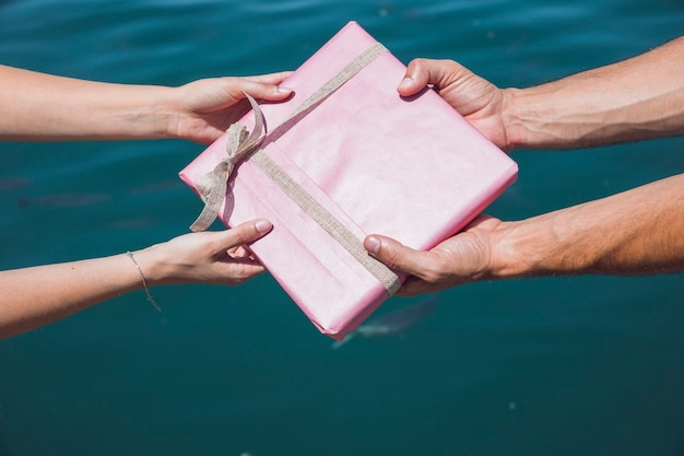 Couple's hand holding pink gift box in front of sea water backdrop