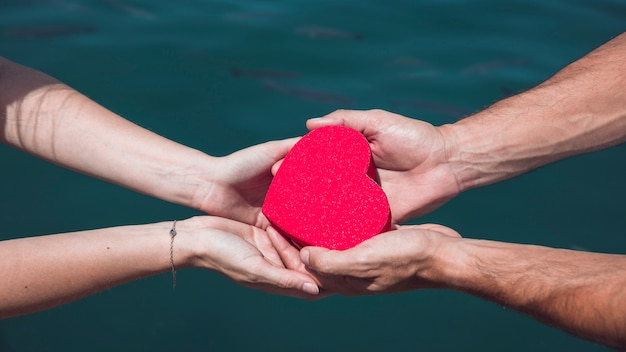 Couple's hand holding red heart shape against sea water background