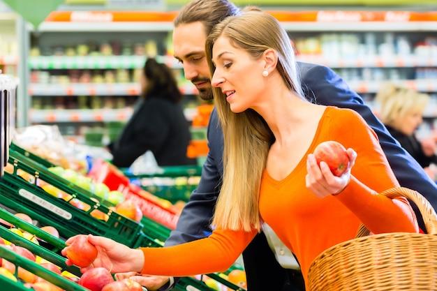 Пара выбирает яблоки во время покупки продуктов в супермаркете