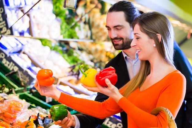 Couple selecting vegetables in hypermarket