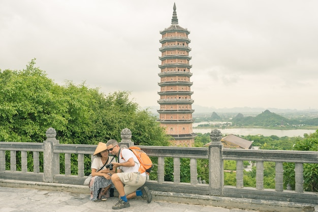 Couple selfie at bai dinh pagoda ninh binh. tourists visiting the biggest buddhist temple complex in vietnam