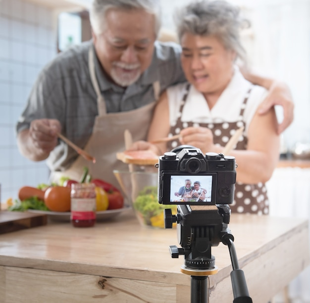 Couple senior asian elder happy living in home kitchen. grandfather and grandmother wiping bread with jam vlog vdo for social blogger. . modern lifestyle & relationship.