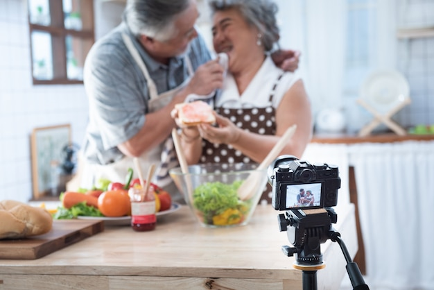 Couple senior asian elder happy living in home kitchen. grandfather wiping grandmother mouth after eating bread with jam vlog vdo for social blogger.