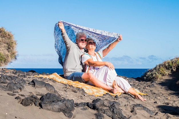 Couple of senior caucasian hippy style and life rest on the rocky beach in tenerife. colors and alternative lifestyle for totally freedom concept near the ocean. alternative colorful clothes to live f