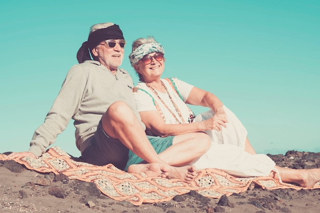 Couple of senior caucasian hippy style and life rest on the rocky beach in tenerife. colors and alternative lifestyle for totally freedom concept near the ocean.. happiness for nice cheerful people