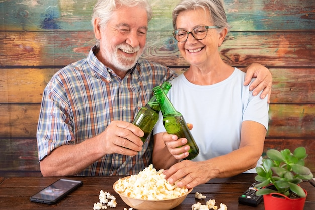 Couple of senior having fun with beer and popcorn. sitting and smiling at wooden table. focus on beer bottles in hand