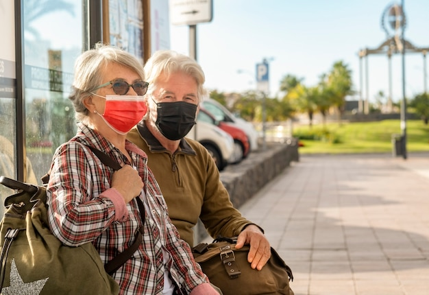 Couple of senior travelers sitting on the bench while waiting for the bus wearing a surgical mask
