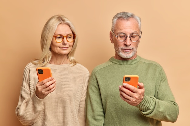 Couple of senior woman and man use modern smartphones focused in displays read news online wear casual jumpers isolated over brown studio wall