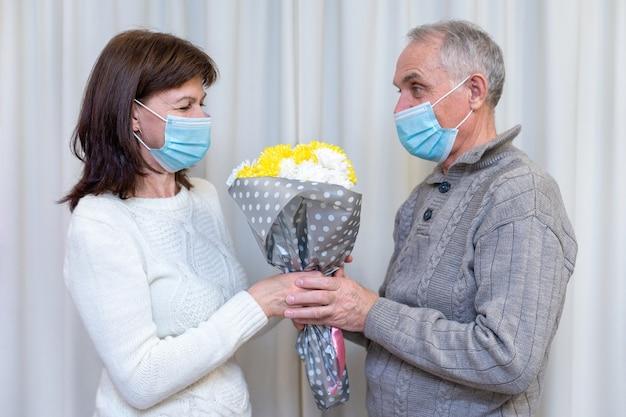 Пара пожилых людей празднует день святого валентина в маске.