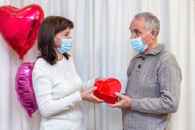 Couple seniors celebrate valentine's day in mask.