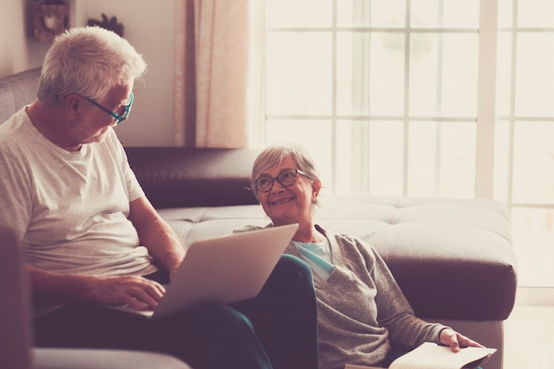 Couple of seniors at home - man with laptop and glasses sitting at the sofa - woman sitting on the grund reading a book - indoor and love concept