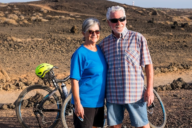 Couple of seniors married together looking something at the rocky mountain with their two bikes . active mature man and woman lifestyle