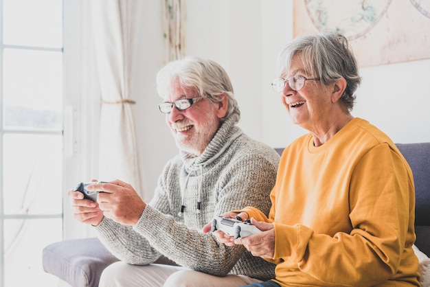 Couple of seniors and mature people looking and the tv and using controllers playing video games at home together on the sofa - lockdown lifestyle indoors