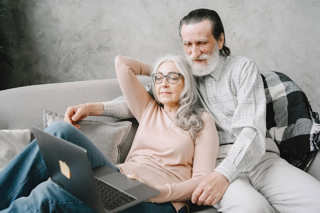 Couple of seniors smiling and looking at the same laptop hugged on the sofa
