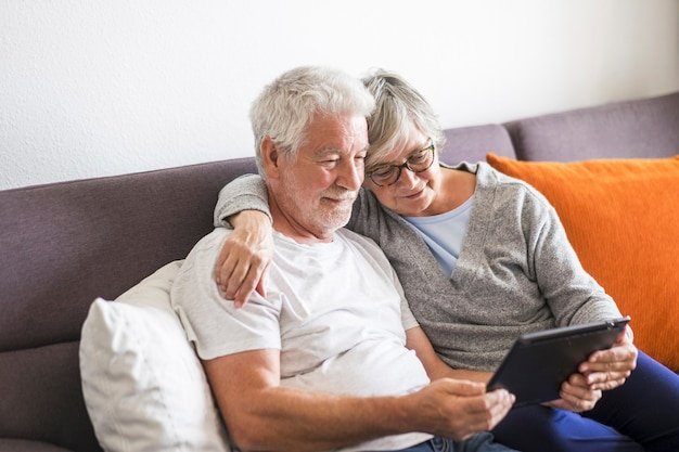 Couple of seniors smiling and looking at the same tablet hugged on the sofa - indoor, at home concept - caucasians mature and retired man and woman using technology