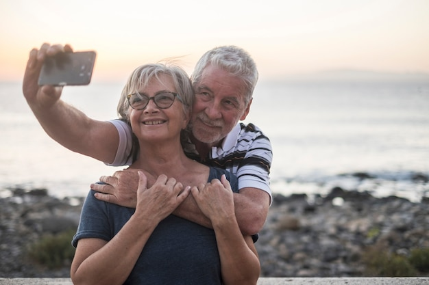 Couple of seniors taking a salfie at the beach - hapy married retired couple enjoying - woman with glasses