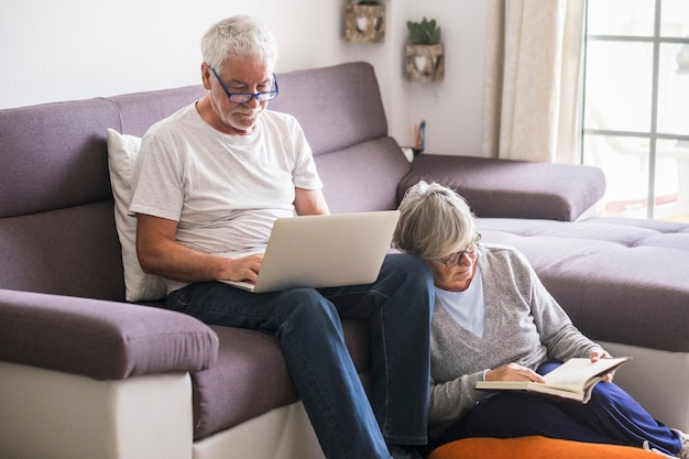 Couple of seniors together a home - mature man working sitting on the sofa or watching videos with his wife sitting on the ground reading a book in silence - caucasian retired indoor