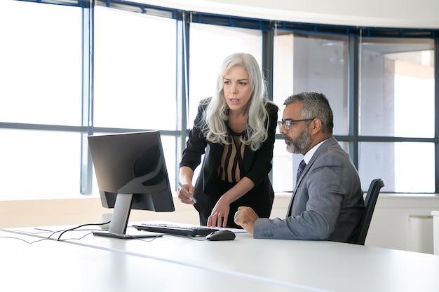 Coppia di colleghi seri discutendo il contenuto sul monitor del computer, indicando il display e parlando seduti nella sala riunioni con finestra panoramica. concetto di comunicazione aziendale