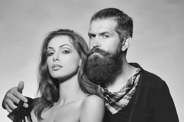 Couple of sexy woman with bare shoulders and handsome bearded man with long beard portrait of intimate passionate sensual people