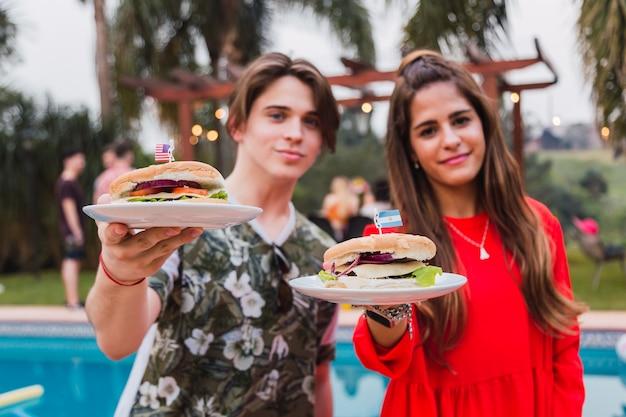 Пара делится гамбургером. флаги страны. лето и концепция еды.