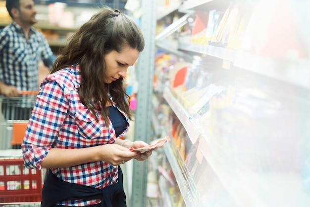 식료품 가게에서 함께 재료를 쇼핑하는 커플