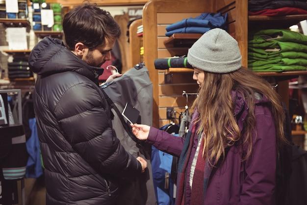 洋服店で買い物をするカップル