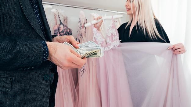 高級ファッションブティックでのカップルの買い物。手に現金を持っている金持ち