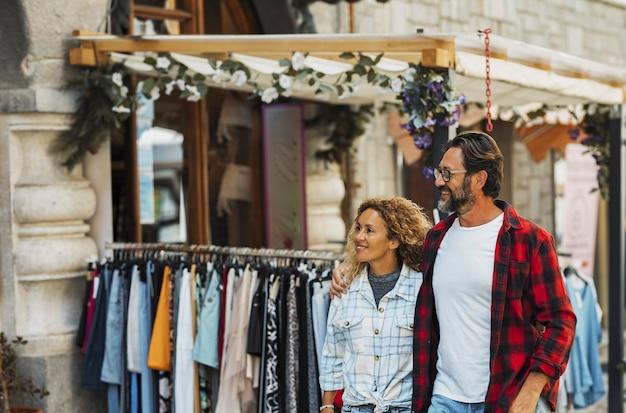 街の通りで買い物をするカップル。街の通りを歩きながら抱きしめるカップル。通りを歩き回っている間楽しんでいる幸せなカップル。