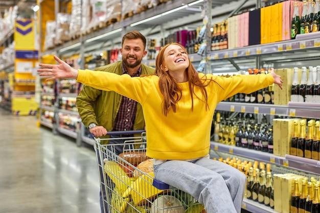 식료품 슈퍼마켓에서 함께 쇼핑하는 커플, 남자는 빨간 머리 여자 친구를 카트에 들고, 그들은 재미 있고, 시간을 즐기고, 여자는 행복하고, 팔을 벌립니다.